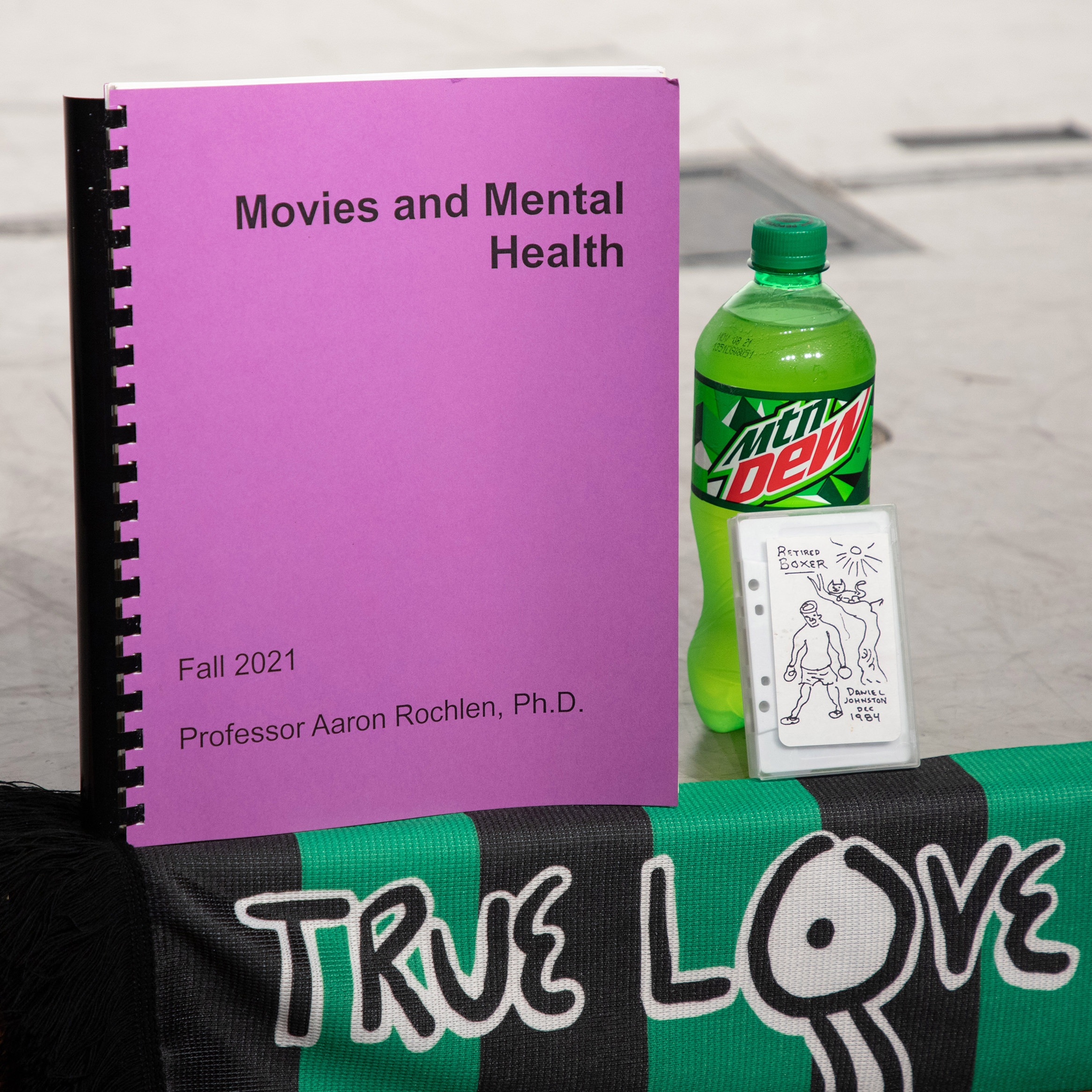 The course packet for Movies and Mental Health with Daniel Johnston memoribilia