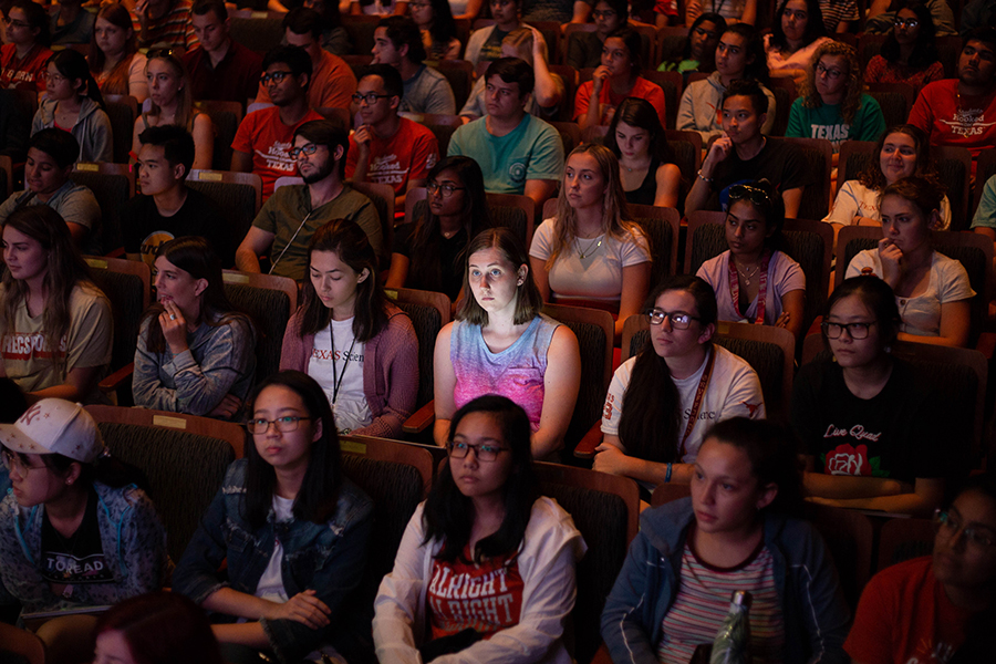 Dozens of students sitting in an auditorium with one student illuminated