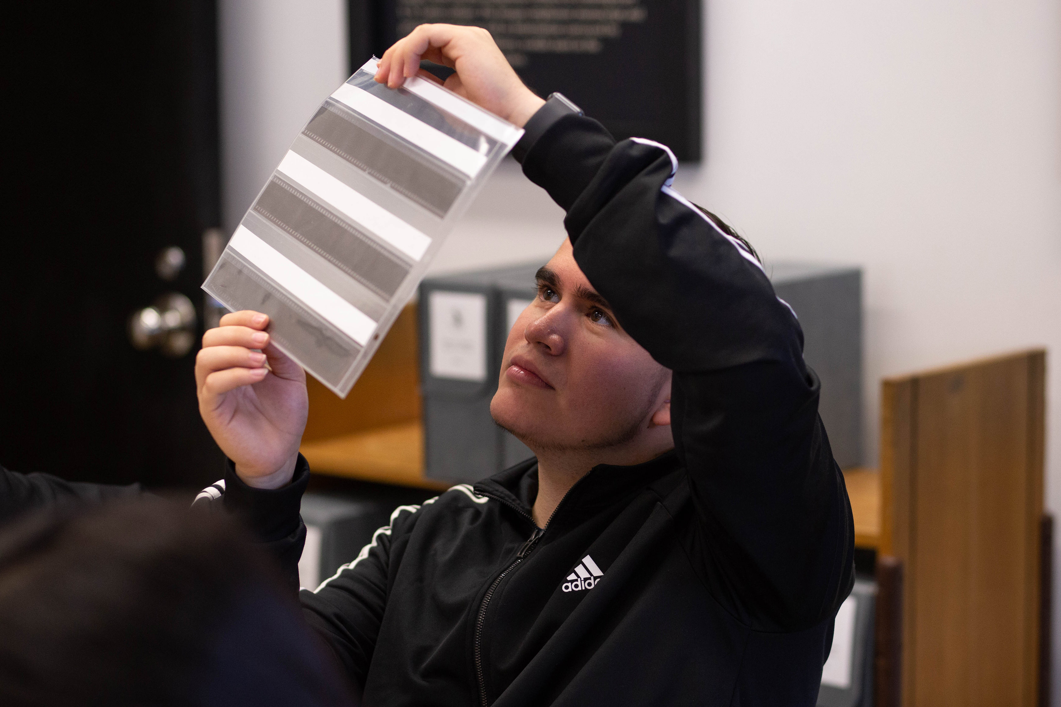 A student examines strips of 35mm film