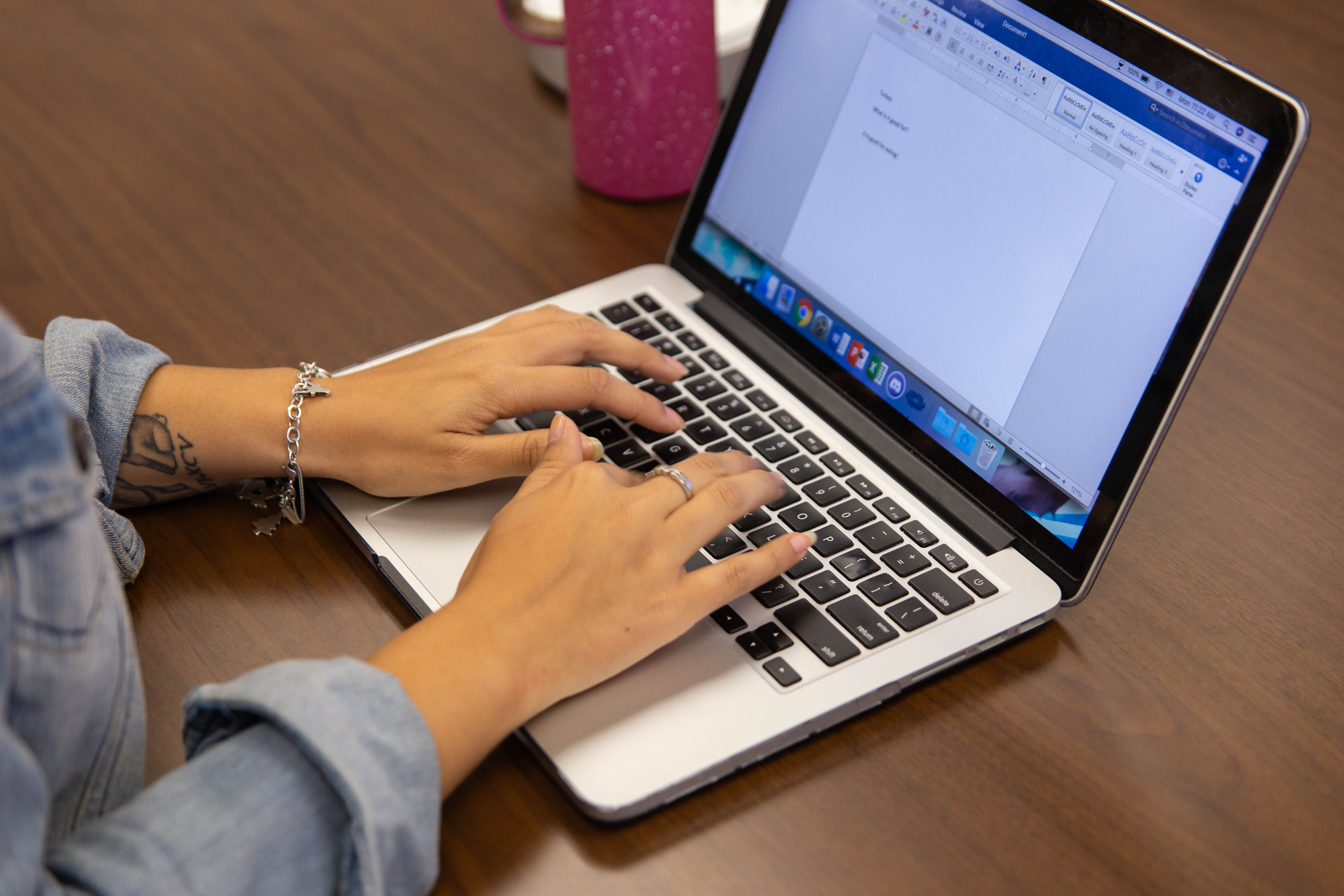 A student typing on her laptop keyboard