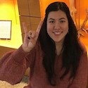 Image of Emily Prines sitting in front of skeleton display case in the UT Anthropology department, giving the Hook Em Horns sign